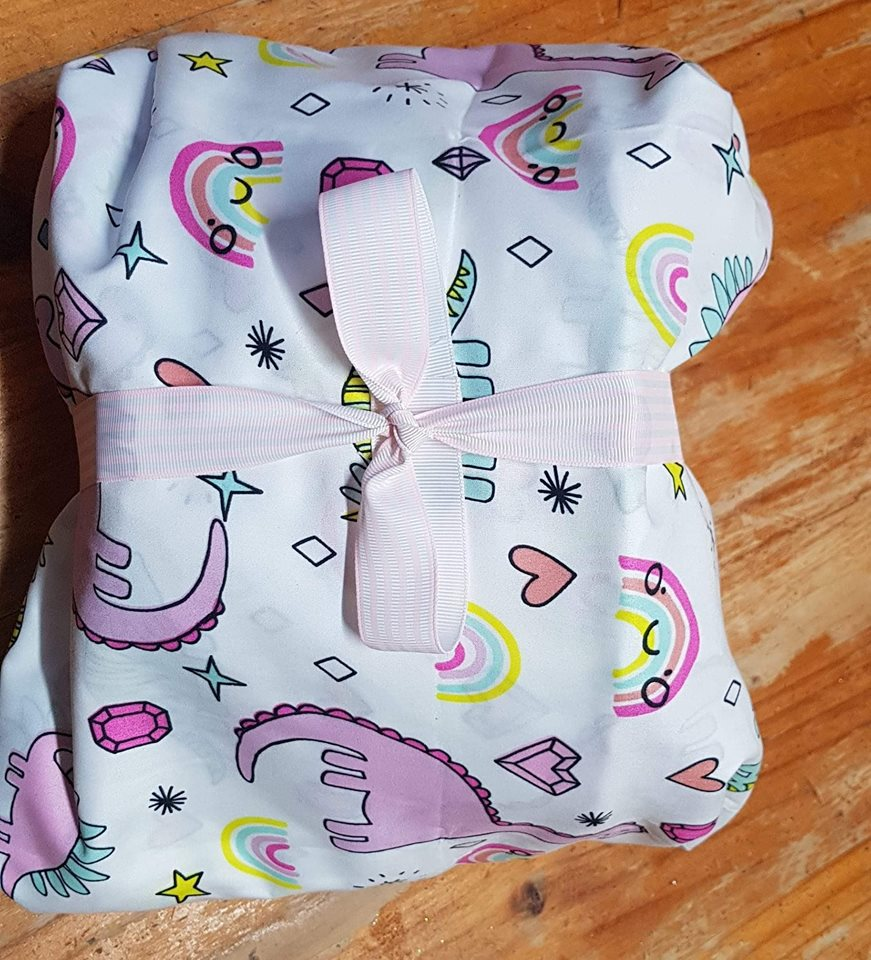 Photo of a young girl's gifts wrapped in a new sheet set Furoshiki style.