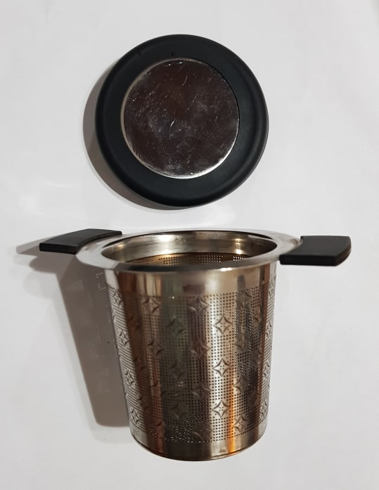 A photo of a stainless steel tea infuser which sits inside a mug.