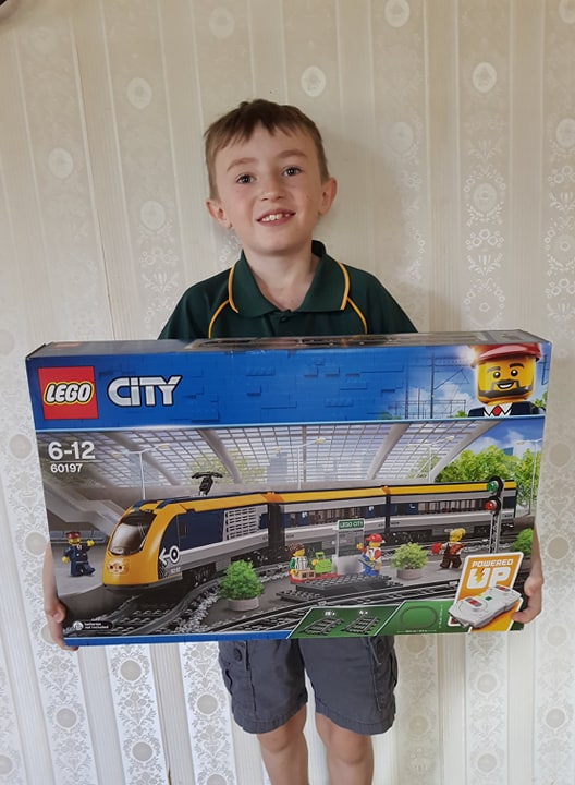 The proud moment a seven year realises he has enough money to purchase his saving goal - a Lego train.